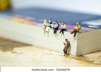 Reading and hobby concept. Group of miniature mini figures businessman, man and woman siting and read a book together on a big book on vintage world map.
