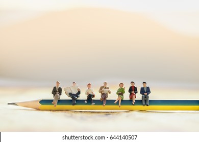 Reading, hobby and relaxation concept.  Group of businessman and business woman  miniature figures sitting, talking and waiting on pencil with copyspace for text