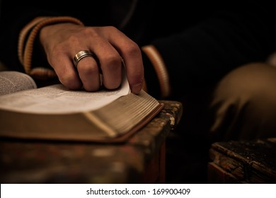Reading Holy Bible on vintage table with candle, closeup