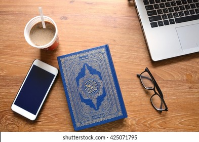 Reading The Holy Quran(Islamic Book) on Wooden table.