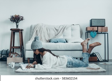 Reading interesting story. Beautiful young woman in casual wear and knit hat reading book while lying on the floor at home