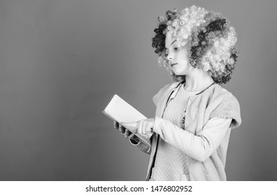 Reading jokes. Time to have fun. Circus school. Study hard. Ridiculous story. Reading funny book. Literature club. Jokes book concept. Kid colorful curly wig artificial hair clown style hold book.