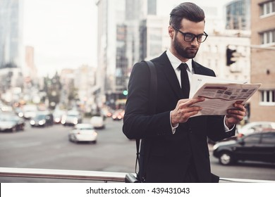 Reading the latest news. Confident young man in full suit reading newspaper while standing outdoors with cityscape in the background