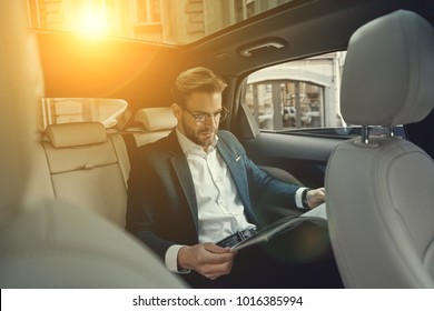 Reading latest news. Handsome young man in full suit reading a newspaper while sitting in the car