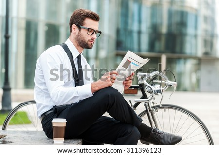 Reading the latest news. Side view of young businessman reading newspaper while sitting near his bicycle with office building in the background