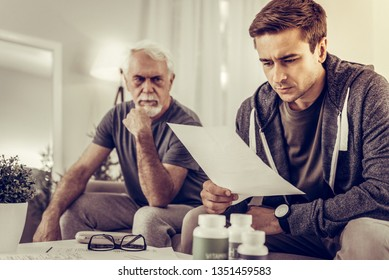 Reading medical assessment. Focused blue adult son reading the assessment of doctor of his ill aged upset grey-haired father sitting on the sofa beside him
