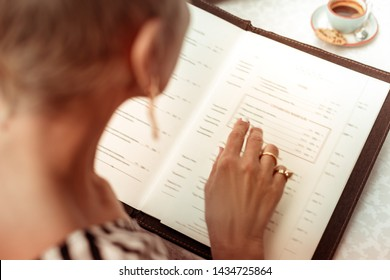 Reading the menu. Top view of woman wearing nice rings reading the menu in restaurant sitting at summer terrace