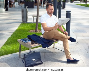 Reading a newspaper, sitting on bench