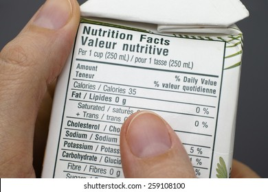 Reading a nutrition facts on box with coconut water.