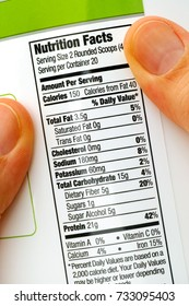 Reading nutrition facts on protein jar. Close-up.