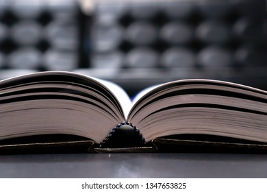 Reading old textbook in university library, read book or relaxing in vintage black background. Reading is complex cognitive process of decoding symbols to derive meaning communication information.
