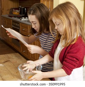 Reading a Recipe. Two sisters are about to make gingerbread for Christmas. The older is reading the recipe while her five year old sister waits patiently.