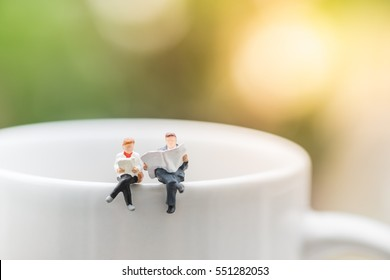 Reading, relaxing, hobby concept. Close up of two miniature mini people figures man and woman sit and read a book and a newspaper on the cup of hot coffee.