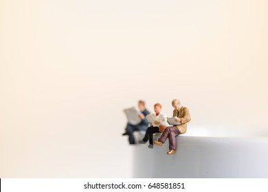 Reading, relaxing, hobby concept. Close up of group miniature mini figures man and woman sit and read a book and a newspaper on the cup of hot coffee.