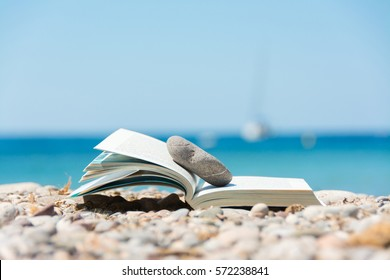 Reading in summer vacation, concept. Book on the pebble beach in Mallorca