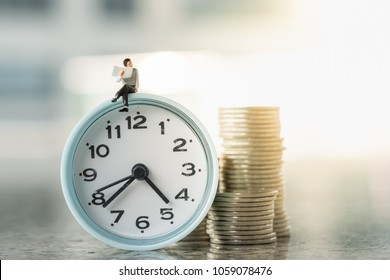 Reading,  Time and Business concept. Businessman miniature figures siting and reading a newspaper on vintage round clock with stack of coins.