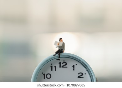 Reading,  Time and Business concept. Businessman miniature figures siting and reading a newspaper on vintage round clock.