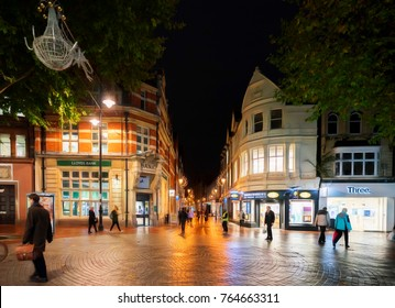 Reading, UK. 14th November 2017. People are seen walking along a shopping street in Reading, UK at night.