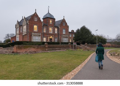 READING, UK - CIRCA MARCH 2015: A student walks near the Old Whiteknights House,  a modernised Victorian building which hosts the Graduate School of University of Reading.