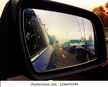 Reading, UK - December 1 2018: Looking at queuing traffic in the wing mirror of a car.