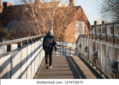 Reading, UK - December 2016: Backview of a young man with backpack passing a bridge in a sunny day.