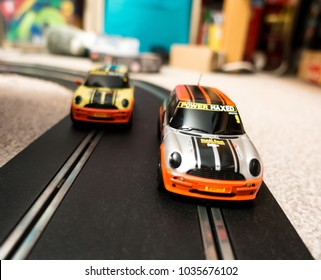 Reading, UK - February 24, 2018: A close up view of two toy slot cars on a racing track in a child's bedroom.