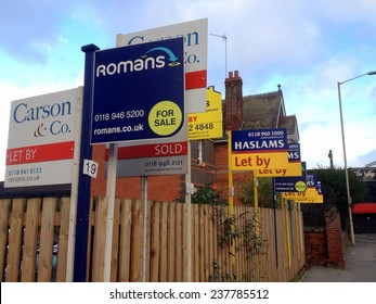 Reading, United Kingdom - December 11th, 2014: Estate Agency or Real Estate business advertising signs crowded together in a residential district of Reading, England on December 11th 2014