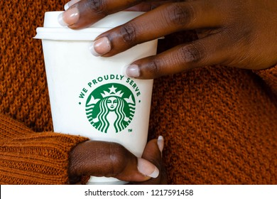 Reading, United Kingdom- October 31-2018 : African woman wearing warm  autumn winter knitwear jumper holding a cup of Starbucks coffee with logo and we proudly serve tagline for brand