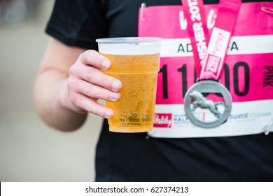 READING,UK-MARCH 19,2017:Hand with cup of beer and medal  after finished half marathon in Reading on 19 march 2017.