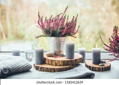 Ready for autumn. Common heather flower in zinc pot, home decor idea.  Set of cozy seasonal decorations on window sill. Gray candles lit, wooden boards, common pink heather flower in flower pot.