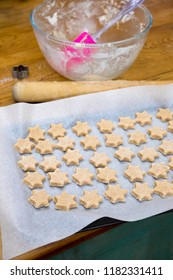 Ready to bake biscuits: cookie dough in star shapes on baking sheet, with pink spatula, mixing bowl, cutter and rolling pin on messy domestic kitchen bench top