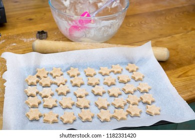 Ready to bake: cookie dough in star shapes on baking sheet, with pink spatula, mixing bowl, cutter and rolling pin on messy domestic kitchen bench top