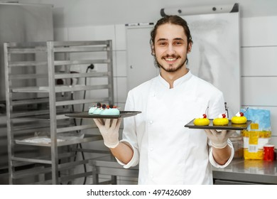 Ready to be served. Shot of a handsome smiling young chef holding two plates with glazed cakes posing at his kitchen