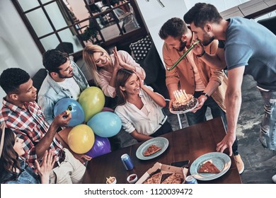 Ready to blow the candles? Top view of happy people celebrating birthday among friends and smiling while enjoying a party