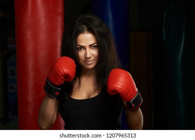 Ready to boxing young woman. Pretty sporty brunette girl in red boxing gloves