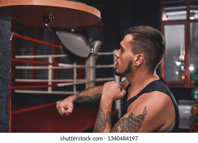 Ready to break his record. Close-up of muscular tattooed boxer in sports clothing hitting punching speed bag while exercising in boxing gym