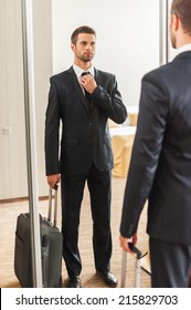 Ready for business trip. Confident young man in formalwear adjusting his necktie while standing against mirror in hotel room