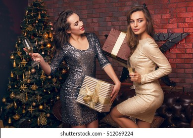 Ready for celebration. Portrait of two pretty young girls, girls offer Christmas gifts to each other and drinking champagne. Christmas party.