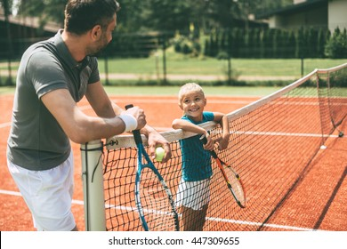 Ready to play? Cheerful father and daughter leaning at the tennis net and looking at each other with smiles