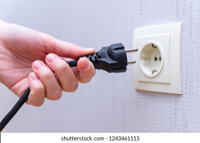 Ready to connect. Plugging electrical, black plug in electric socket on wall.