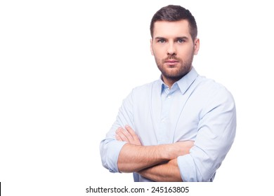 Ready to do great things. Handsome young man in shirt looking at camera and keeping arms crossed while standing against white background