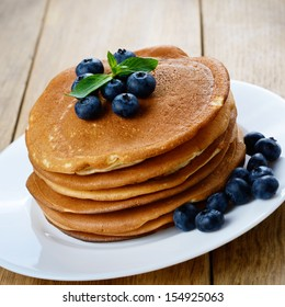 Ready to eat pancakes with blueberries on white plate
