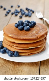 Ready to eat pancakes with blueberries on the white plate