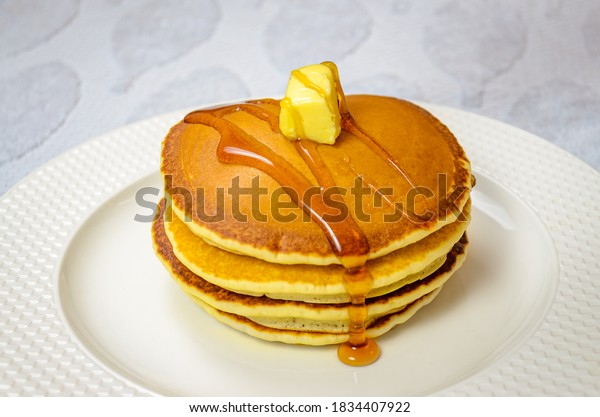 Ready to eat sweet Pancake garnished with honey and butter in a round plate