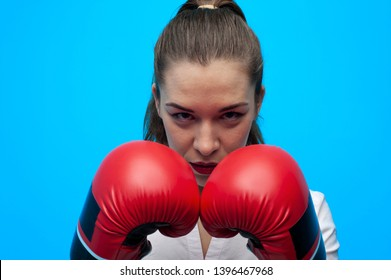 Ready for a fight. Determined business woman wearing boxing gloves. Female boxer wearing formal clothes posing on blue background.