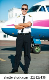 Ready to flight. Full length of confident male pilot in uniform keeping arms crossed and smiling with airplane in the background