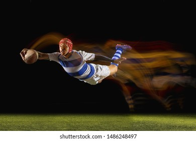 Ready to fly for win. One caucasian man playing rugby on the stadium in mixed light. Fit young male player in motion or action during sport game. Concept of movement, sport, healthy lifestyle.