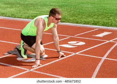 Ready to go. Shot of a fit young man athlete standing at the starting blocks ready to sprint copyspace on the side