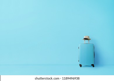 Ready to go, travel concept. Single suitcase in empty blue room with copy space
