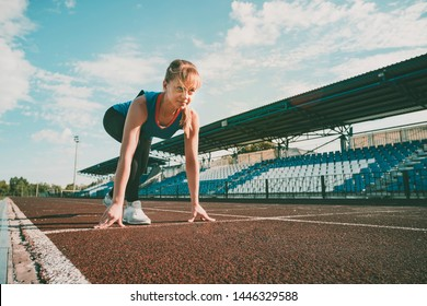 Ready to go. Young fitness blonde girl wearing blue top, black tights, sneakers and pony-tail on the starting line of stadium track, preparing for a run. Healthy lifestyle concept.